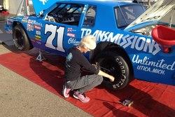 Ellie Cesario checks tire pressures on the #71 Dave Marcis NASCAR Historic 1979 Oldsmobile