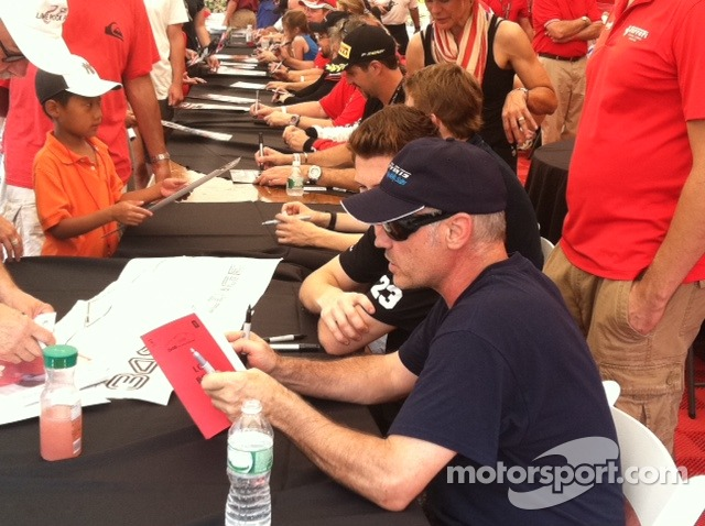 John Farano signs a log book from the original year of the Ferrari Challenge series